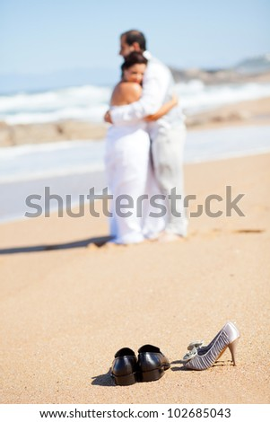 bride and groom hugging on beach, focus on shoes - stock photo