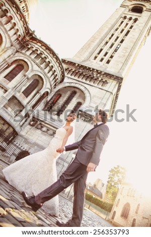 Bride and groom in front of a church - stock photo
