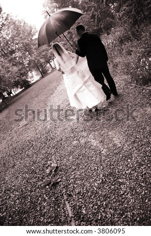 bride and groom in rain - stock photo