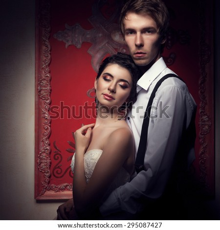 Bride and groom in rococo interior on red vintage background. Just married. Happy young couple. Beautiful bride in white wedding dress - stock photo