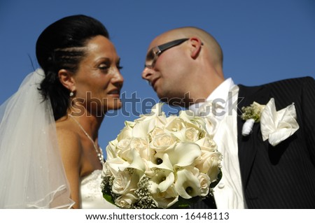 Bride and groom is showing their wedding bouquet while looking at each other. - stock photo
