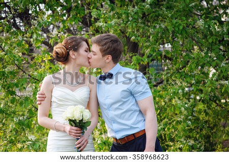 bride and groom kiss in the spring garden. - stock photo