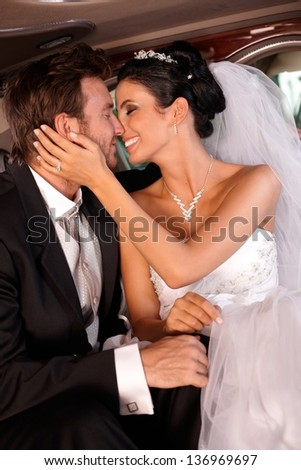 Bride and groom kissing in limousine, embracing. - stock photo
