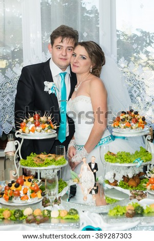 Bride and groom kissing near the holiday table. Wedding banquet, buffet table - stock photo
