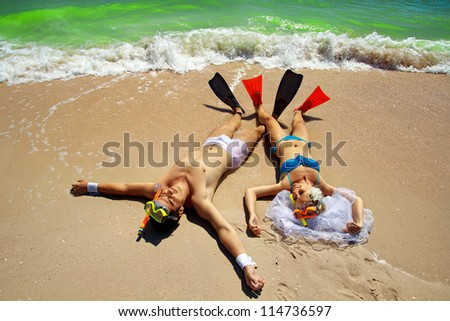 Bride and Groom lying on beach shore in  fins - stock photo