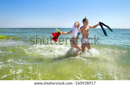 Bride and Groom lying on beach shore with fins  - stock photo