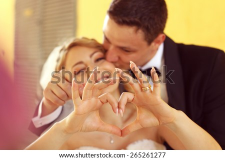 Bride and groom making love sign with their hands  - stock photo