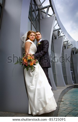 Bride and groom near collonnade - stock photo