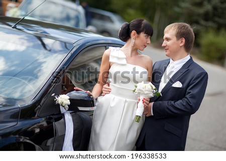 bride and groom near the car - stock photo