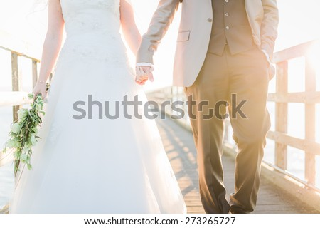 Bride and groom on pier walking towards camera holding hands - stock photo