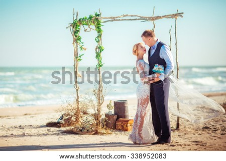 Bride and groom on their wedding day on the beach - stock photo