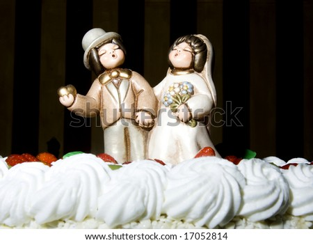 Bride and Groom on Top of a wedding cake - stock photo