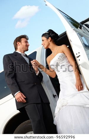 Bride and groom on wedding-day getting out of limousine.? - stock photo