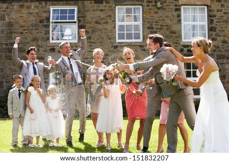 Bride And Groom Opening Champagne In Front Of Guests - stock photo
