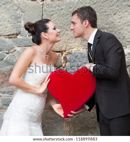 Bride and groom outdoor portrait with red heart - stock photo