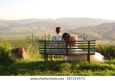 Bride and groom outside garden wedding on bench with African Natal Midlands mountain scenery background - stock photo