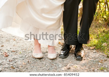 Bride and Groom Playfully Show Off Their Shoes - stock photo
