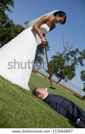 Bride and groom playing golf  - stock photo