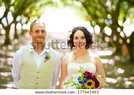 Bride and groom pose for a portrait in a backlit orchard on their wedding day in Oregon with light filtering through the trees. - stock photo