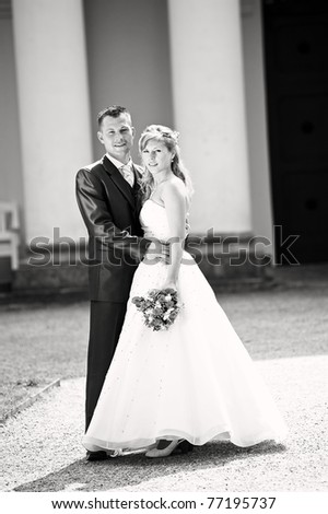 Bride and groom posing in mansion area - stock photo