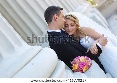bride and groom posing in the city near big white columns - stock photo
