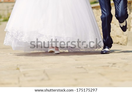 bride and groom running in sunny day - stock photo