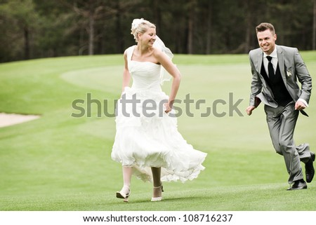bride and groom running on the green grass - stock photo