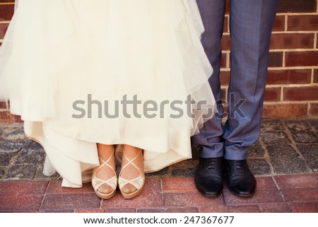 Bride and groom's feet on wedding day - stock photo