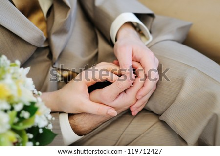 Bride and groom's hands - stock photo