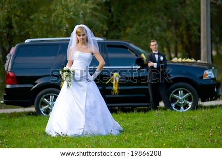 Bride and groom standing in front of black wedding car - stock photo