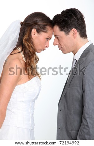 Bride and groom standing on white background with upset look - stock photo