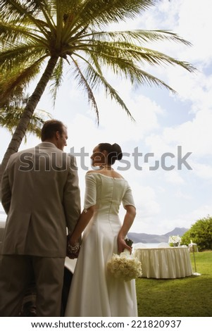 Bride and groom under palm tree - stock photo