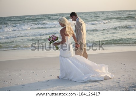 Bride and Groom Walking Along the Beach - stock photo