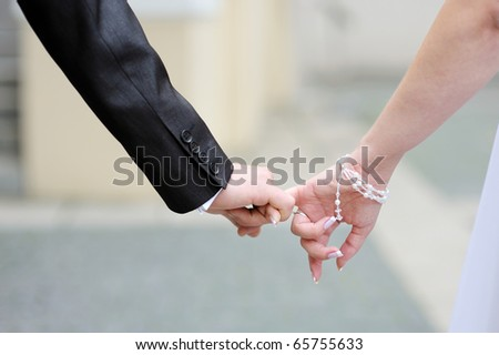 Bride and groom walking together holding their hands - stock photo