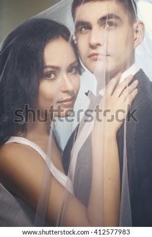 Bride and groom - wedding elegant photo. Couple together under bridal veil - stock photo