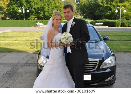 Bride and groom with wedding car - stock photo