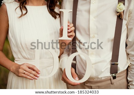 bride and groom with wooden words i do - stock photo