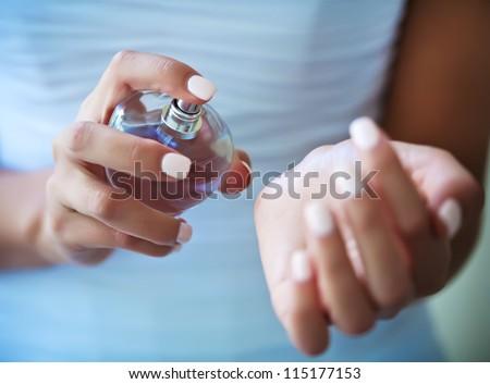 bride applying perfume on her wrist - stock photo