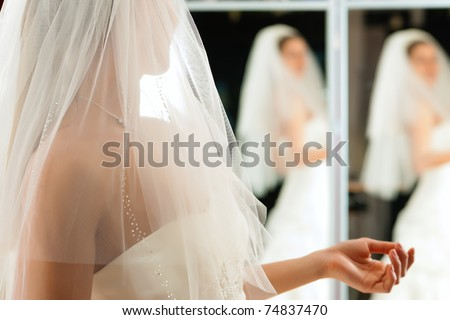 Bride at the clothes shop for wedding dresses; she is choosing a dress - stock photo