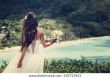 bride, beautiful young girl with dark hair in a white wedding dress with bouquet on  background of beach with blue water. Seychelles - stock photo