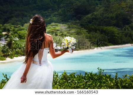 bride, beautiful young girl with dark hair in white wedding dress with bouquet on background of beach with blue water. Seychelles - stock photo