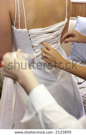Bride being laced up into her wedding dress by multiple helpers. - stock photo