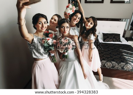 Bride & bridesmaids posing with bouquets, taking selfie - stock photo