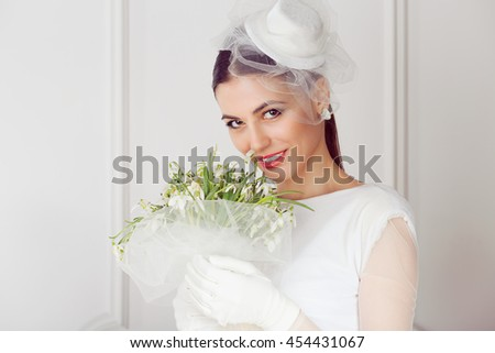 Bride. Closeup portrait smiling happy adult young woman retro style looking at you camera holding smelling lilies Lilly of the valley flowers isolated classic background. white dress gloves fascinator - stock photo
