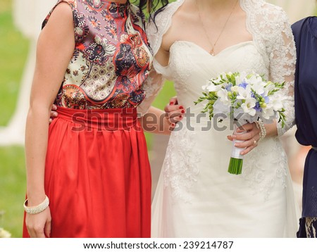 bride embracing bridesmaid in red dress - stock photo