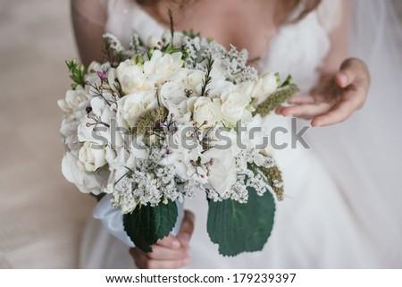 Bride gently touchs her wedding bouquet. - stock photo