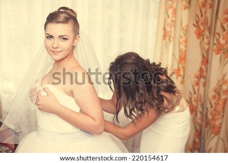 Bride getting ready. beautiful bride in white wedding dress with hairstyle and bright makeup. Happy sexy girl waiting for groom. lady in bridal dress have final preparation for wedding. - stock photo