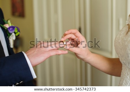 Bride groom puts the ring on his hand on the wedding day. - stock photo