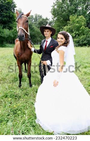 bride groom walking a horse in a field - stock photo