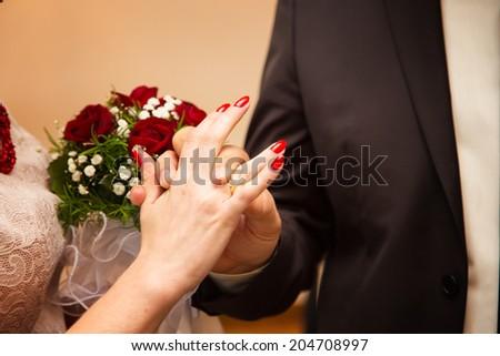bride groom wears the ring wedding - stock photo